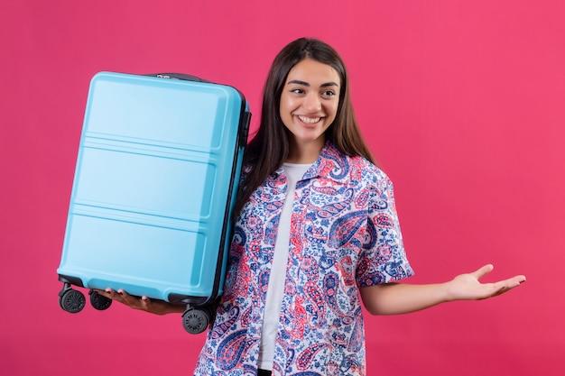 ピンクの壁に陽気に手を広げてスーツケースの肯定的で幸せな笑顔を保持している若い美しい旅行者女性