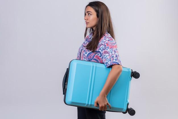 Молодая красивая женщина путешественника, держащая чемодан боком с серьезным лицом по изолированной белой стене