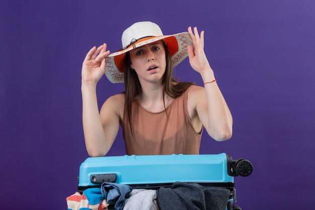 紫色の壁に彼女の帽子に触れて混乱している服の完全なスーツケースと夏の帽子の若い美しい旅行者の女性