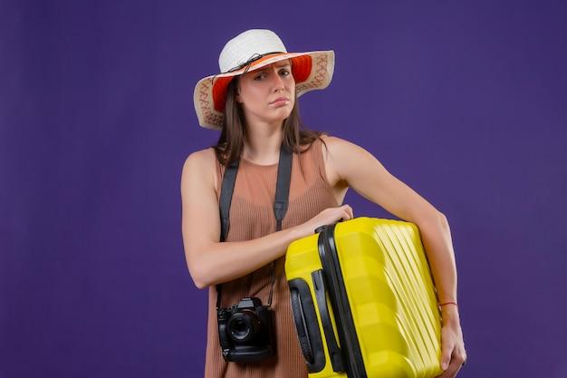 黄色のスーツケースとカメラを探して混乱している紫色の壁に答えがなくて混乱している夏の帽子の若い美しい旅行者の女性