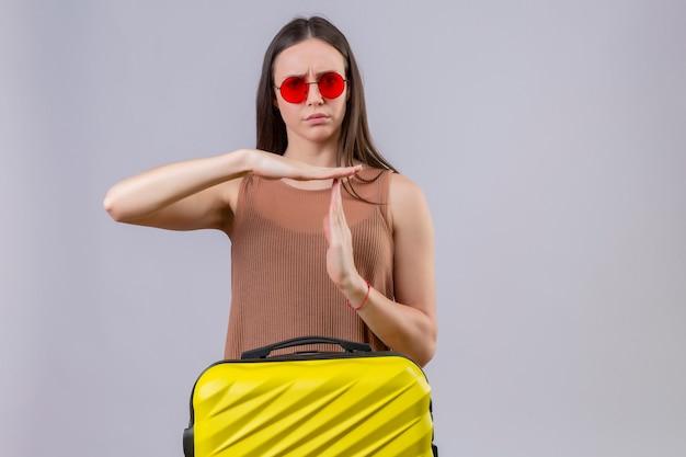 ピンクの壁の上に立って手で疲れた不満を作るタイムアウトジェスチャーを探して旅行スーツケースに赤いサングラスをかけている若い美しい女性