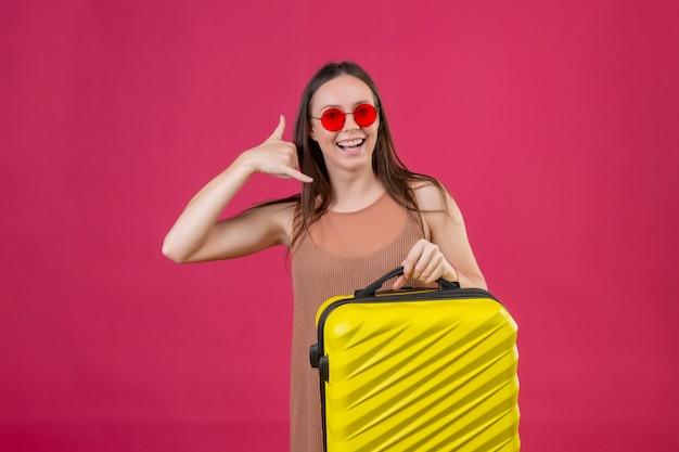 Молодая красивая женщина в красных солнцезащитных очках с чемоданом для путешествий называет меня жестом, весело улыбаясь над розовой стеной