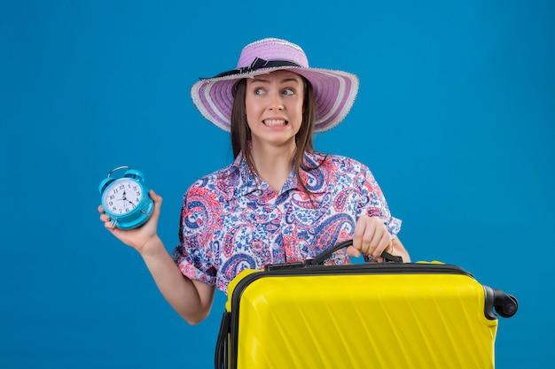 Молодой путешественник женщина в летней шляпе с желтым чемоданом держит будильник подчеркнул и нервничать над синей стеной