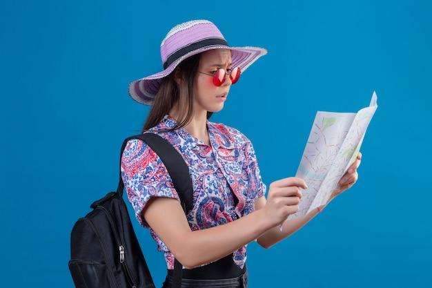 青い壁に眉をひそめている顔でそれを見て地図を保持している赤いサングラスをかけている夏帽子の若い旅行者女性