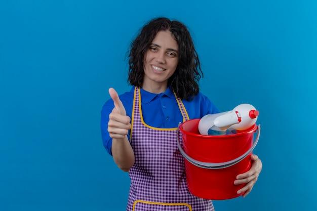 青い壁を越えて陽気な示す親指を笑ってクリーニングツールでバケツを保持しているエプロンを着た若い女性