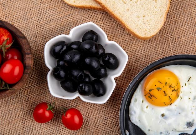 Крупным планом вид черных оливок в миску с томатным хлебом и жареным яйцом на вретище