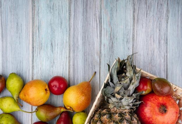 Закройте вверх по взгляду плодоовощей как слива персика гранатового дерева ананаса в корзине и на деревянной поверхности
