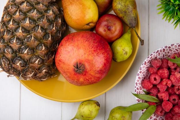 Крупным планом вид фруктов как ананас гранатовый персик в тарелку с малиной в миску на деревянной поверхности