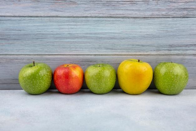 コピースペースを持つ木製の表面にカラフルで新鮮なリンゴの側面図