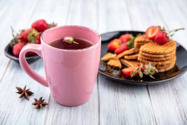 それで花とお茶のカップと木製の表面のプレートにイチゴとワッフルビスケットの側面図