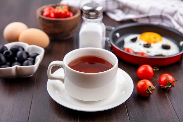 木の表面に紅茶とトマトの目玉焼き黒オリーブ塩のカップの側面図