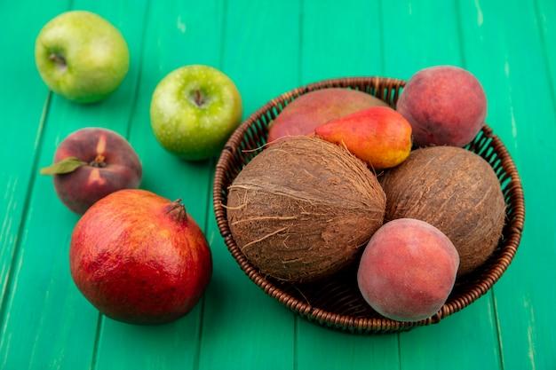 Вид сбоку различных фруктов, таких как кокосовое персиковое яблоко гранатовая груша на ведро на зеленой поверхности