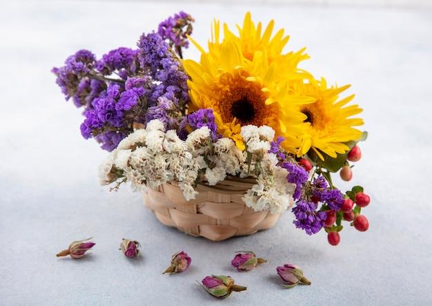 Вид сбоку цветов в корзине на белой поверхности