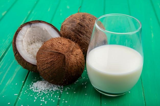Вид сбоку свежих и коричневых кокосов с стакан молока на зеленой поверхности