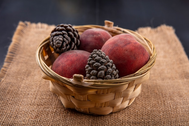 Вид спереди свежих персиков с шишками на ведро на мешок ткани на черной поверхности