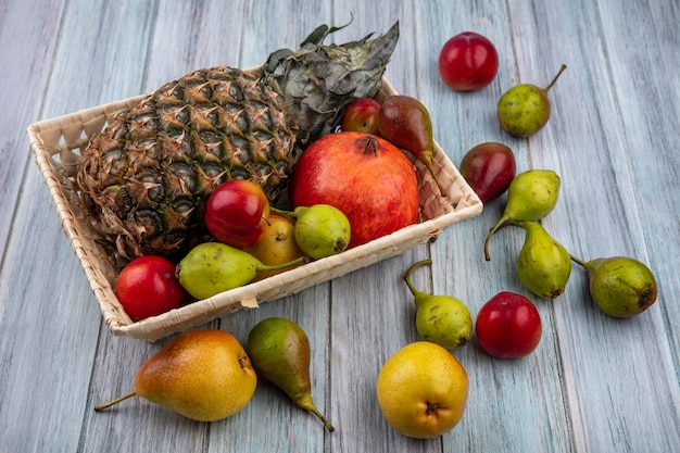 バスケットと木製の表面にパイナップルザクロ桃プラムとして果物の正面図