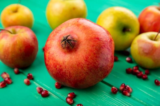 緑の表面にザクロとリンゴとして果物の正面図