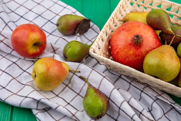 Вид спереди фруктов в виде граната и персика в корзине и на клетчатой ткани на зеленой поверхности