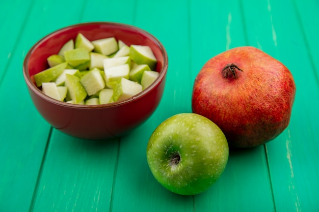 緑の表面にザクロと赤いボウルにみじん切りのスライスと青リンゴの正面図