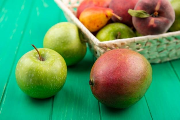 Вид спереди зеленых яблок с различными фруктами, как груша персик на ведро на зеленой поверхности
