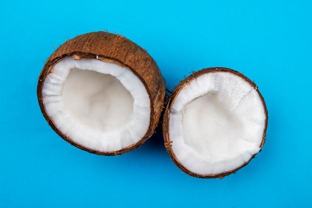 青い表面に大きな新鮮な茶色のココナッツの半分の正面図