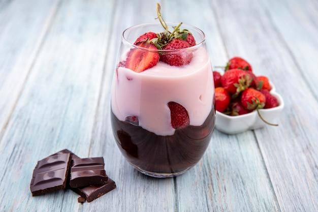 灰色の木製の表面にチョコレートバーとグラスにチョコレートとイチゴのミルクセーキの正面図