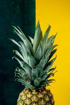 Вид сбоку ананаса на зеленой и желтой поверхности