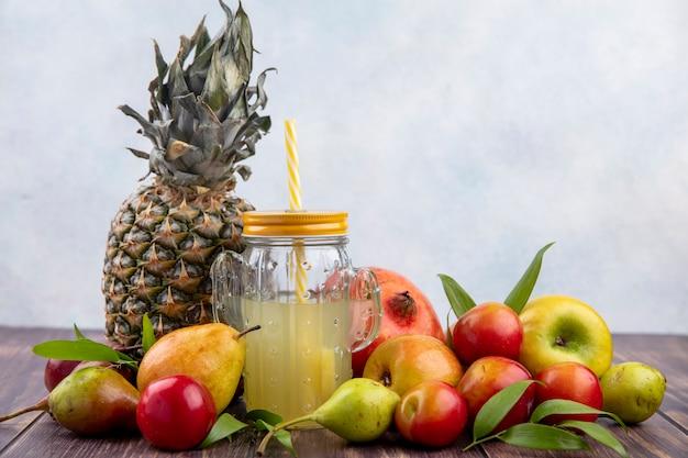 木製の表面と白い表面にパイナップルピーチプラムアップルザクロとしてフルーツとパイナップルジュースの正面図