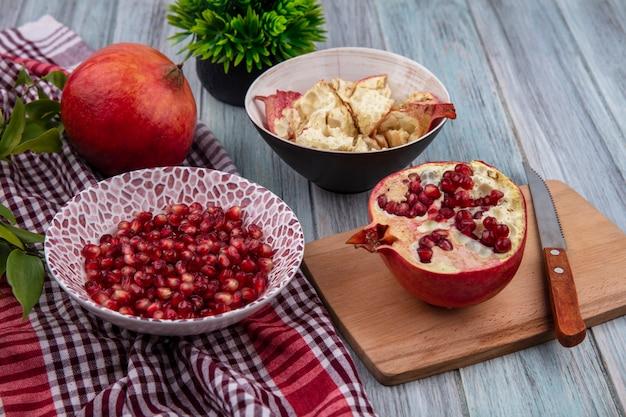 Вид спереди ягод граната в миске с целым и листьями на клетчатой ткани и половину с ножом на разделочной доске с миской гранатовой оболочки на деревянной поверхности