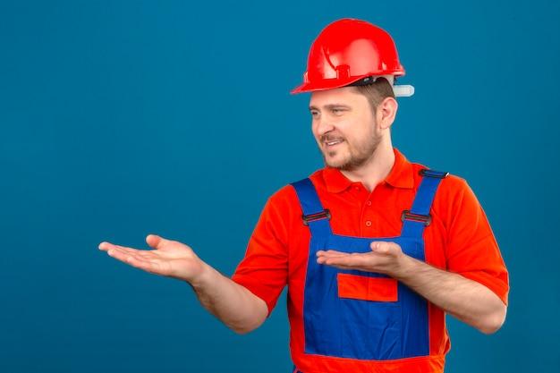 建設の制服とセキュリティヘルメットを提示し、孤立した青い壁に自信を持って笑顔の手のひらで側を指しているビルダーの男