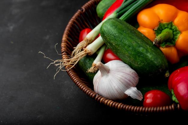 黒の表面に野菜がいっぱい入ったかご