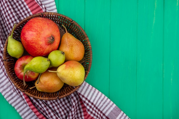 緑の表面の格子縞の布の上のバスケットに果物のトップビュー