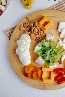 Вид сверху на сырную тарелку с орехами на столе