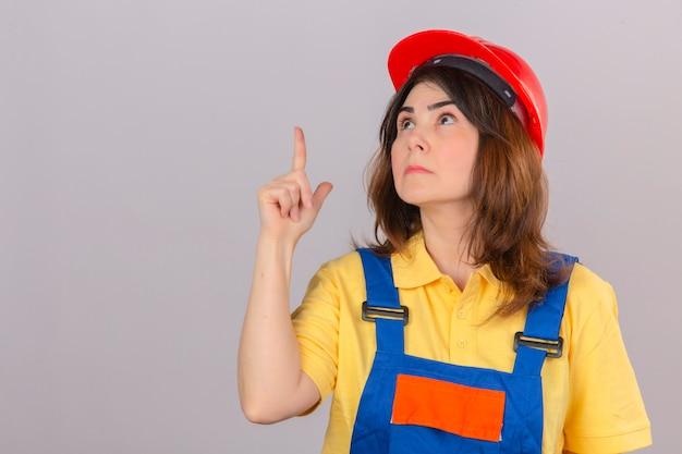 ビルダーの女性が着ている建設の制服と安全ヘルメットを探して、孤立した白い壁に興味がある何かに指でパンティング