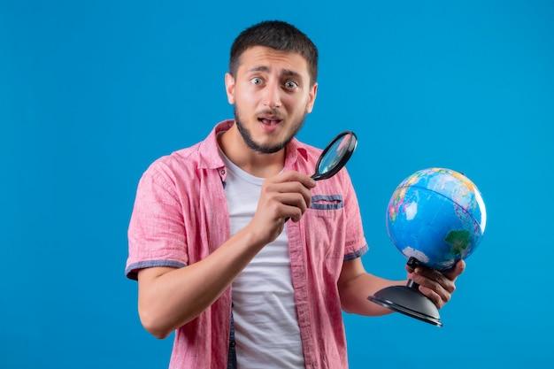 グローブを押し、虫眼鏡を使用してそれを見て若いハンサムな旅行者の男を見て青い背景の上に立って驚いた