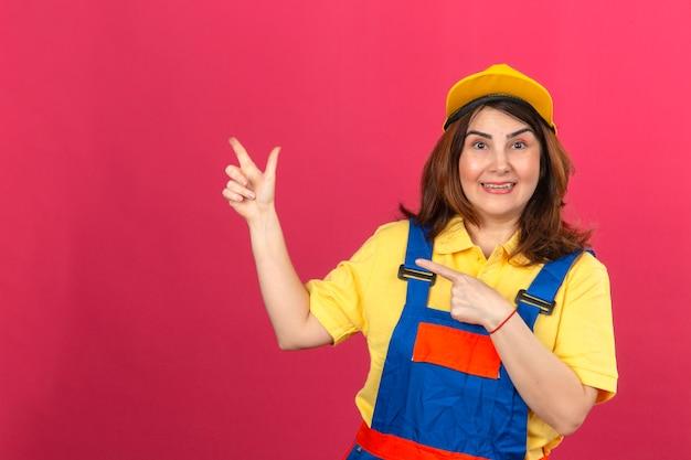 孤立したピンクの壁の上の側に手と指で指している笑顔の建設の制服と黄色の帽子を身に着けているビルダー女性