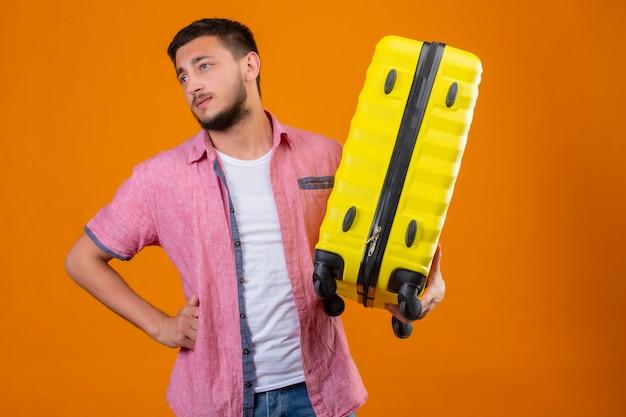 オレンジ色の背景の上に立っている顔に退屈と悲しそうな表情で疲れているよそ見スーツケースを保持している若いハンサムな旅行者男