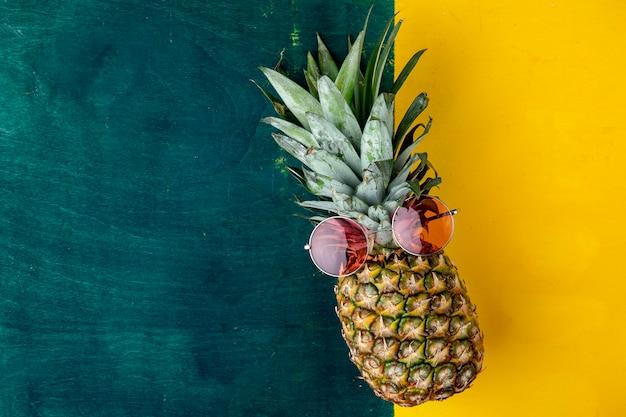 Вид сверху ананас с красными бокалами