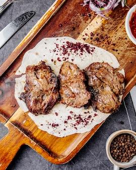 Вид сверху кусочки жареного мяса на деревянной доске