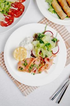 Вид сверху карпаччо из лосося с лимоном и свежим салатом на белой тарелке
