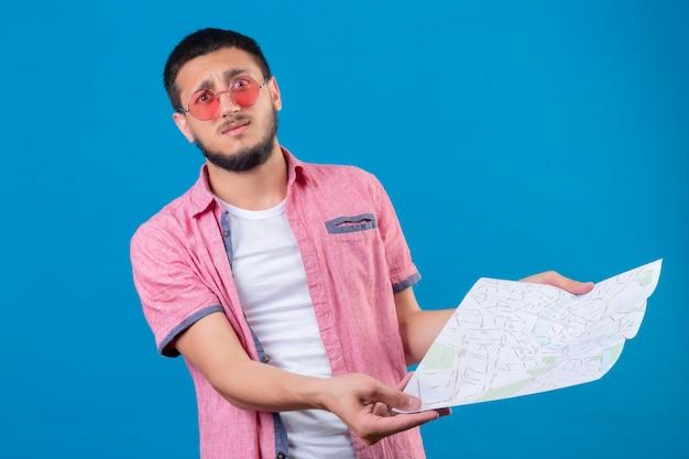 青い背景に失望して立っている地図を探しているサングラスをかけている若いハンサムな旅行者男