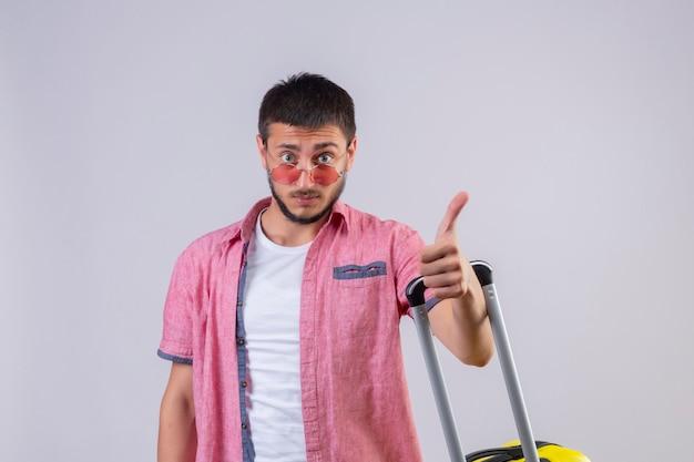 若いハンサムな旅行者の男がカメラを見てスーツケースを持って立っているサングラスを身に着けている白い背景の上に正と幸せの親指を表示