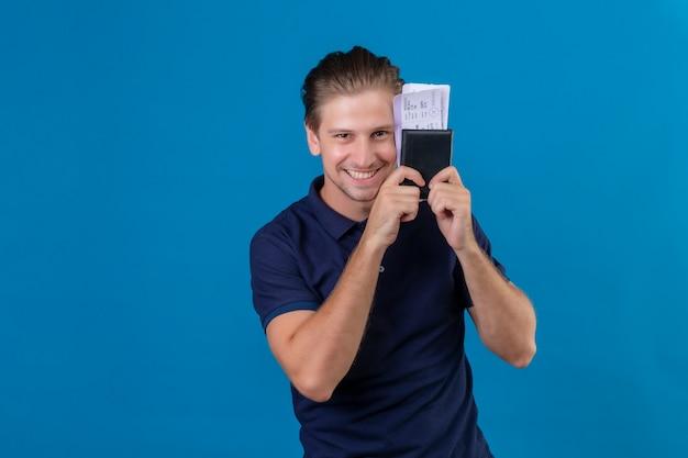 青い背景の上に立っている顔に大きな笑顔でカメラを見て幸せと肯定的な航空券を保持している若いハンサムな旅行者男