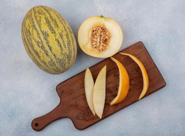白い表面の木製キッチンボード上の皮とメロンのトップビュー