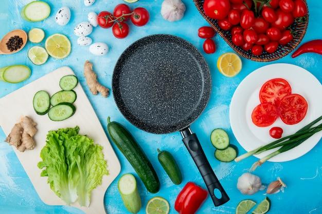 青い表面にレタス、キュウリ、生姜などの野菜とフライパンとレモンのトップビュー