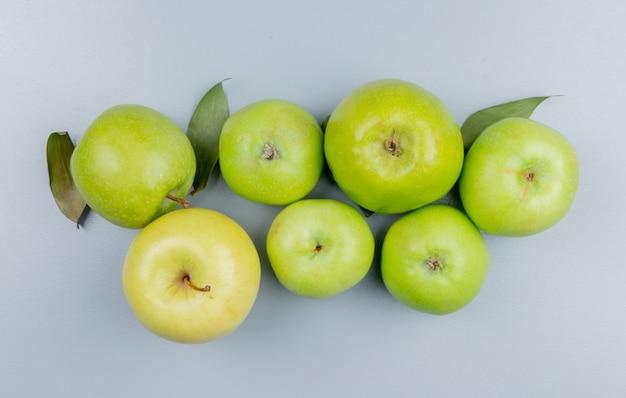 灰色の背景に緑のリンゴのパターンのトップビュー