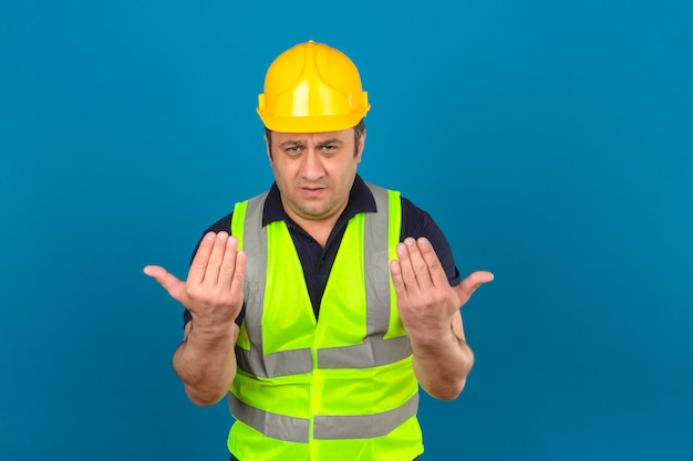 建設の黄色のベストと孤立した青い壁を越えて方向に誰かを導く安全ヘルメットを身に着けている中年の男