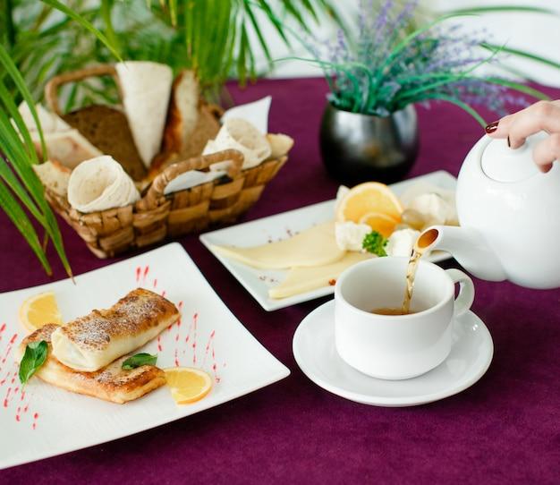 クレープと朝食のティーポットからお茶を注ぐ女性