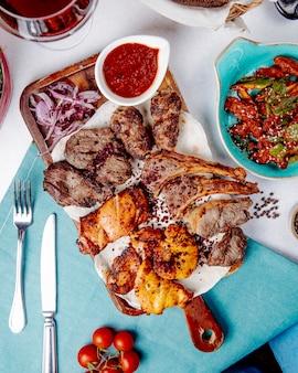 Вид сверху мясного шашлыка с луком специями и свежим салатом