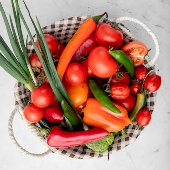 白い表面に野菜がいっぱい入ったかごの上から見る
